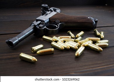 Historic Luger P08 Parabellum handgun and shiny 9 mm bullets on wooden vintage background