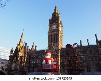 Historic Manchester Town Hall Designed by architect Alfred Waterhouse decorated for festive season with a figure of Father Christmas in Albert square, UK.