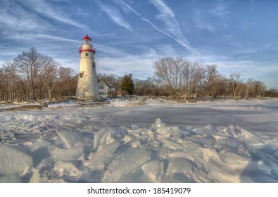 The historic Marblehead Lighthouse in Northwest Ohio sits along the rocky shores of Lake Erie. Seen here from out on the frozen lake where large chunks of ice have piled up near shore.