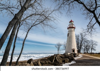 The historic Marblehead Lighthouse in Northwest Ohio sits along the rocky shores of the frozen Lake Erie. Seen here in winter with a colorful sky and snow on the ground.