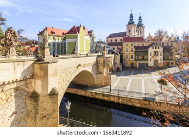 Historic medieval stone bridge over  Mlynowka canal, in Klodzko. Lower Silesia, Poland - connects the Piasek Island and  old town part of city. Behind the bridge is Church of Our Lady of  Rosary - Shutterstock ID 1563411892