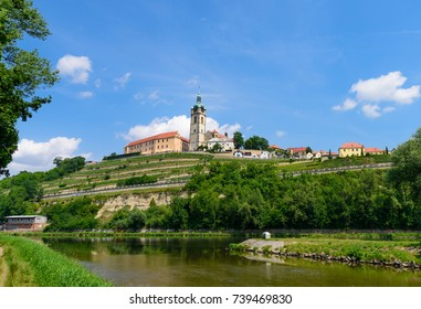The historic Melnik castle and church tower of St. Peter and Paul at the confluence of the Vltava (Moldau) and Labe (Elbe) rivers on sunny early July afternoon in 2017 in Melnik, Czech Republic.