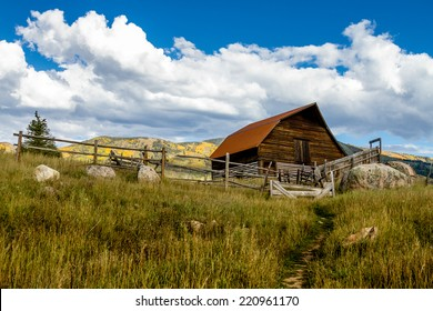 Historic Moore Barn in Steamboat Springs Colorado with mountain slopes filled with fall color on warm autumn afternoon