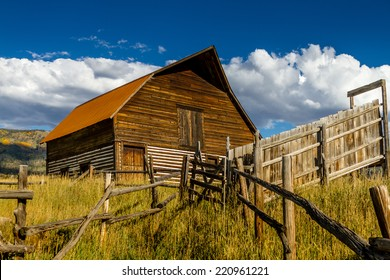 Historic Moore Barn in Steamboat Springs Colorado with mountain slopes filled with fall color on warm autumn evening