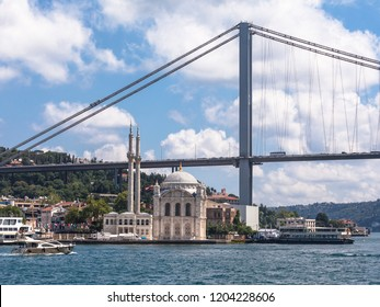 The historic Ortaköy Mosque in Istanbul sits on the edge of the Bosporus strait underneath the modern suspension bridge.