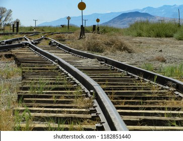 Historic narrow gauge railroad tracks run toward a switch junction and signals in an old rail yard in Laws, California in the Owens Valley with the Sierra Nevada mountains in the distance.