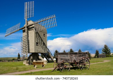Historic old post windmill, unique European design, built to be balanced and rotated into the wind, with wooden sails, blades with and old grain wagon  and old grain wagon.