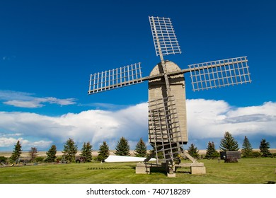 Historic old post windmill, unique design, built to be balanced and rotated into the wind, with wooden sails, blades and old grain wagon.