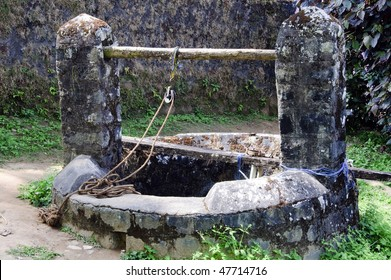 Historic, old traditional water well with rope and pulley in a village in Coorg in Karnataka, India.