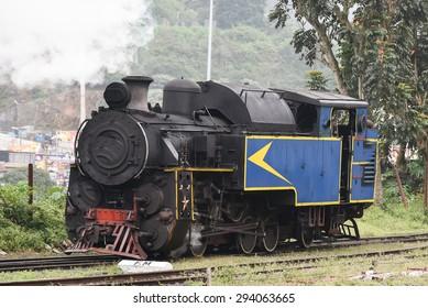 historic old vintage steam engine locomotive train moving down railroad track Nilgiri Mountain Railway Ooty India.