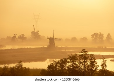 Historic old windmills in a foggy morning in the Doespolder in the village of Leiderdorp in the Netherlands.