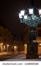Historic and ornamental gas candelabrum in snowy street of Prague. Night image