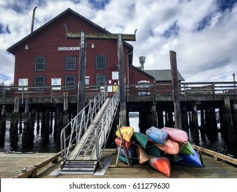 Historic pier and colorful canoes in foreground