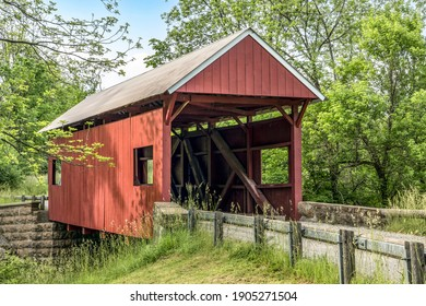 The historic red Erskine Covered Bridge crosses Middle Wheeling Creek in rural wooded Washington County, Pennsylvania.