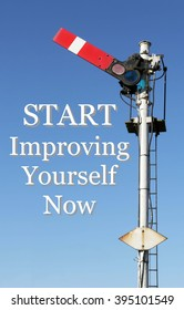 Historic red home British railway signal in the start position with an Inspirational motivational quote of Start Improving Yourself Now against a clear blue sky background.