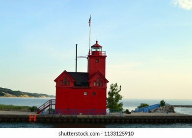 A historic red lighthouse on the coast of Lake Michigan.