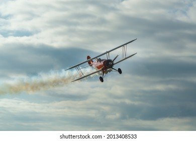The historic red plane flies against the background of clumping clouds.