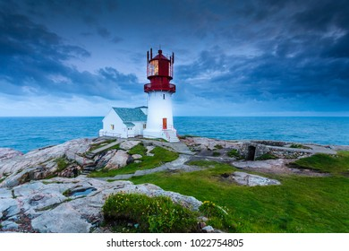 Historic red white lighthouse on the edge of rocky sea coast, South Norway, Lindesnes Fyr beacon