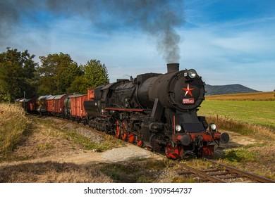 historic retro steam locomotive with freight train