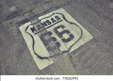 Historic Route 66 marker in Kansas on asphalt.