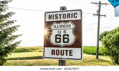 Historic Route 66 Sign With Burst Of Sunlight And Corn Fields In The Background.