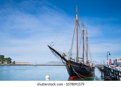 Historic schooner in San Francisco, California, with golden gate bridge at distance