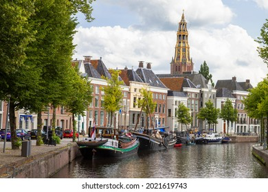 Historic ships, canal houses and warehouses on the old harbor at the Hoge der A with the tower of the historic Der Aa church in Groningen in the background. - Shutterstock ID 2021619743