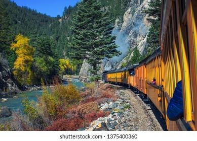 Historic steam engine train travels from Durango to Silverton through the San Juan Mountains along the Animas River in Colorado, USA.