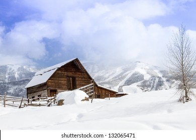 Historic Steamboat Springs barn on snowy hill with ski area lifts and slopes in background