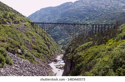 historic steel bridge over the white pass gorge 18 miles north of skagway alaska surrounded by wooded and rocky mountains