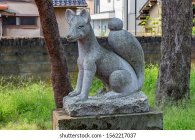Historic stone statue of fox, or kitsune in Japanese, messenger of the God Inari, at Nomachiinari shinto shrine in Kanazawa, Ishikawa Prefecture, Western Japan.