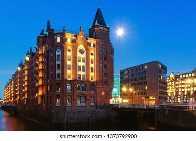 historic store house in famous UNESCO world heritage Speicherstadt in Hamburg with the moon next to a little tower