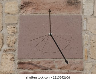 A historic sundial on the facade of a church