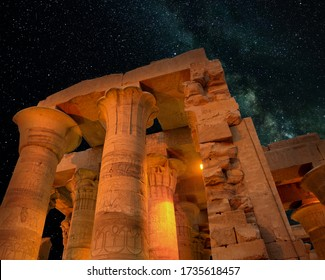 The historic temple of Kom Ombo in Egypt on a romantic night. The building is illuminated with warm light. The sky is clear with many stars. Parts of the Milky Way can be seen.