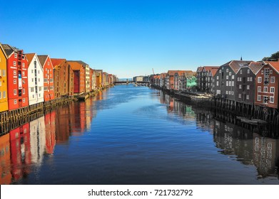 Historic timber buildings line the banks of the River Nidelva in Trondheim, Norway.
