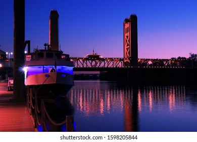 The historic Tower Bridge spanning the Sacramento River is lit up at Blue Hour.  An unidentified tour boat is preparing for a dinner cruise.  People are in non-profile silhouette and unidentifiable.