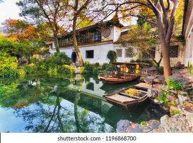 Historic traditional botanic garden in Chinese city Suzhou interior view of architecture around still pond with boats and trees.