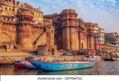 Historic Varanasi city with ancient architecture and tourist boats along the Ganges river bank. Varanasi is a popular tourist destination of India.
