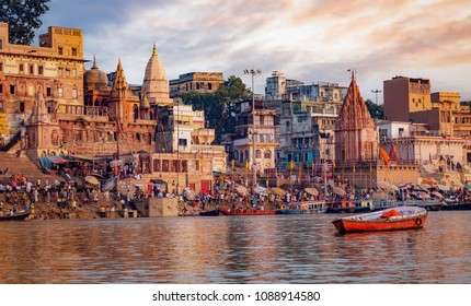 Historic Varanasi city with ancient temples and buildings along the Ganges river ghat as viewed from a boat at sunrise.