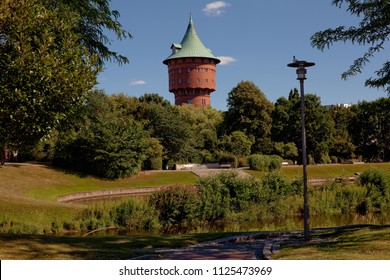 historic water tower made of bricks in Cuxhaven, Germany, seen behind an idyllic park on a sunny summer day
