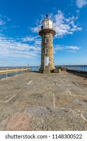 Historic Whitby harbour lighthouse on east pier with a blue sky background.