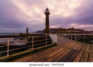 The Historic Whitby West Pier Light looking towards Whitby Abbey and St Hilda's Church in Yorkshire