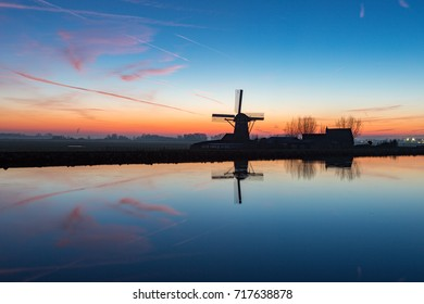 A historic windmill with reflection in the water on the Ringvaart canal in Abbenes the Netherlands.