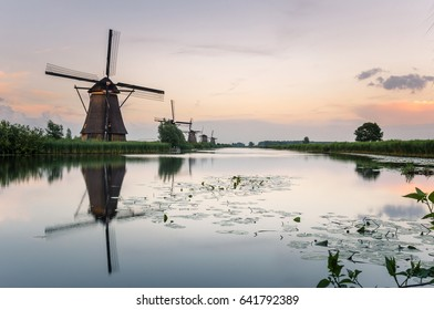 Historic Windmills along a Canal in The Netherlands at Dusk