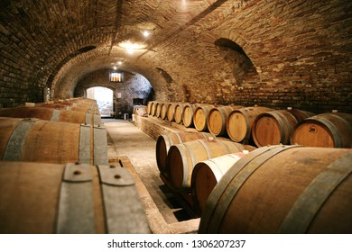 Historic wine cellar in Langhe (Piedmont, Italy) with many barriques and slavonian oak barrels for the aging of red wine. Barolo, Italy - October 2016