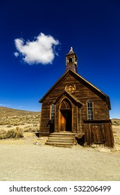 Historic wooden church in the deserted mining town of Bodie in California, with blue sky and one small white cloud above.