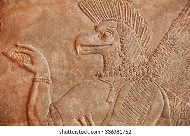 Historical Assyrian relief of bird face genie carrying a cedar-cone, made for Palace at Nimrud in 850BC. Exhibition of artifacts in Pergamon Museum, Berlin.
