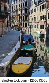Historical buildings and small bridge across a canal with boats in Venice, Italy
