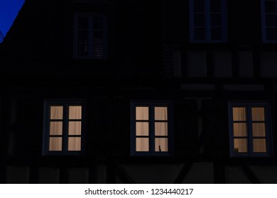 historical buildings windows and lamp light at autumn late evening blue hour sky