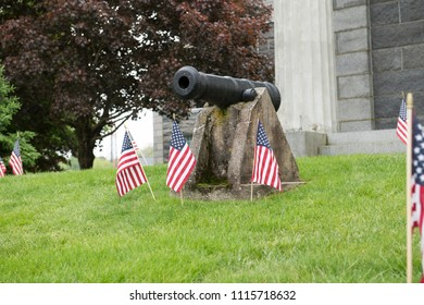 Historical cannon mounted in a lawn is surrounded by American flags to celebrate a patriotic holiday